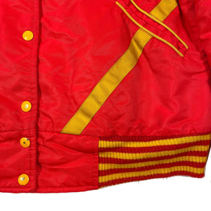 Second Room Vintage Clothing. Vintage University of Calgary Dinnies jacket, which was the U of C's womens basketball team. This red and yellow jacket has a very classic sports feel, with striped cuffs, hood, quilted interior, two front pockets and a very cute embroidered dinosaur logo on the chest. Free North American shipping on all orders.