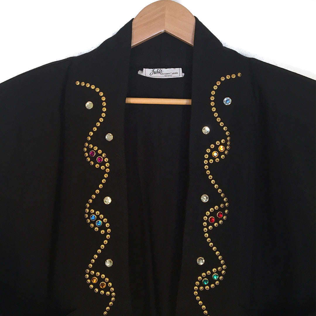 Second Room Shop Vintage. Shop vintage, shop sustainable. Vintage black open coat/jacket, with gold studs and multi colored rhinestones. Two pockets on the front, no buttons or zipper for closure. Full length dolman sleeves, and shoulder pads.