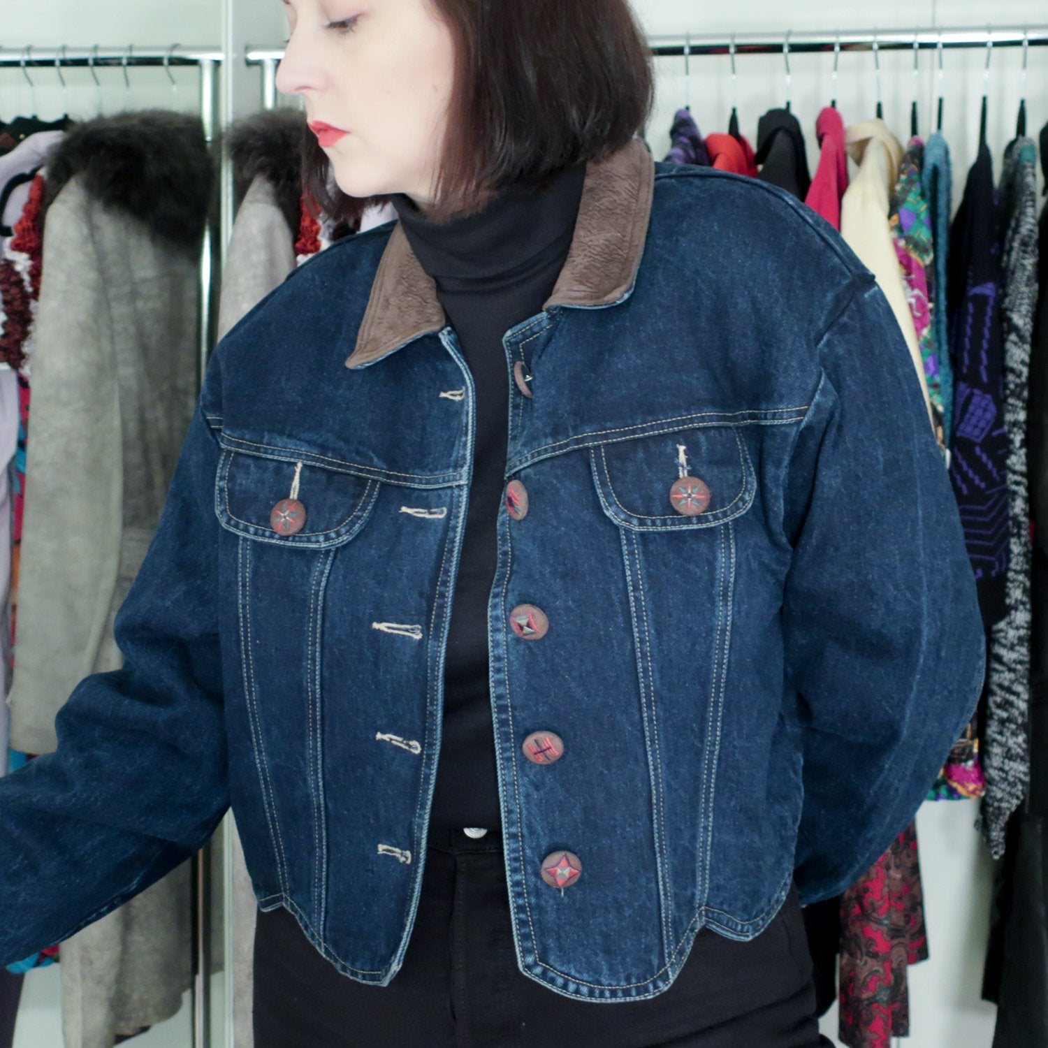 Second Room Shop Vintage. Shop vintage, shop sustainable. Vintage Roughrider denim jacket, with faux suede collar, and cropped scalloped bottom. The buttons on the jacket are the real stars, as they are all faux suede covered, and embroidered with different patterns. The jacket has two front breast pockets, and one button at each cuff.