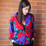 Second Room Shop Vintage. Shop vintage, shop sustainable. Vintage bomber jacket with amazing rose pattern, in red, purple and green. Navy blue ribbed cuffs, and collar. This jacket has two front pockets, one inside pocket with button closure, and subtle shoulder pads.