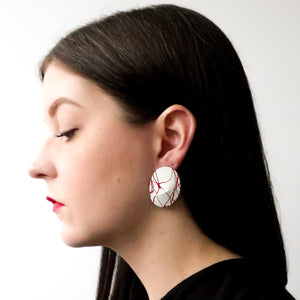 "Second Room Vintage Clothing. Vintage oval, white enamel painted earrings with red paint splatter design. Earrings are 1.25"" wide and 1.5"" tall. Free North American shipping on all orders."