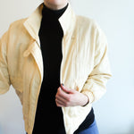 Second Room Vintage Clothing. Vintage pale butter yellow machine washable silk blend quilted bomber jacket, with zipper closure, two front pockets, elastic waist and cuffs, with subtle sewn in shoulder pads. Free North American shipping on all orders.