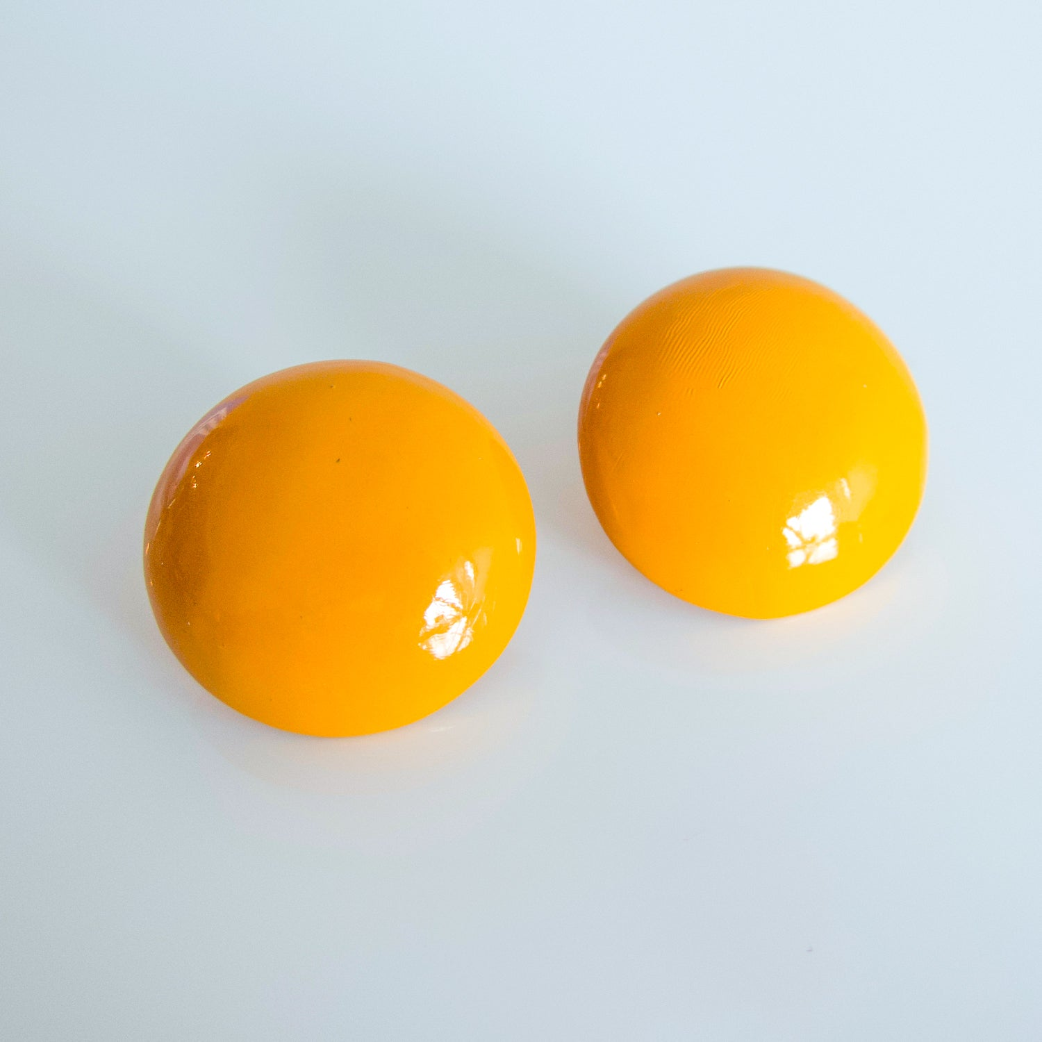 "Second Room Vintage Clothing. Get some egg yolks on your earlobes with these cute mustard yellow, round dome stud earrings! Earrings are 1.25"" across. Original earring backs have been replaced with new, clear silicone backings. Free North American shipping on all orders."