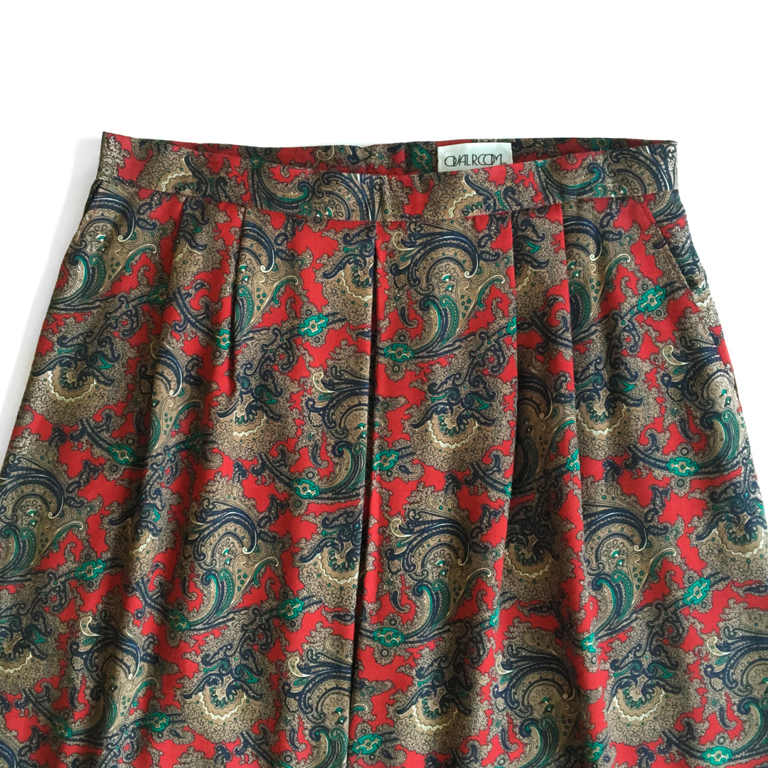 Second Room Shop Vintage. Shop vintage, shop sustainable. Beautiful paisley patterned high waisted vintage midi skirt. Has side pockets, pleats at the waist, and a box pleat at the front. Fully lined, with back zipper and button closure.