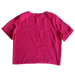 Second Room Shop Vintage. Shop Vintage, Shop Sustainable. Vintage short sleeve bright pink blouse, with round neck line and shoulder pads (easily removed). Cute seaming detail in the front, and fabric covered button closure at back of neckline. Great over size fit.