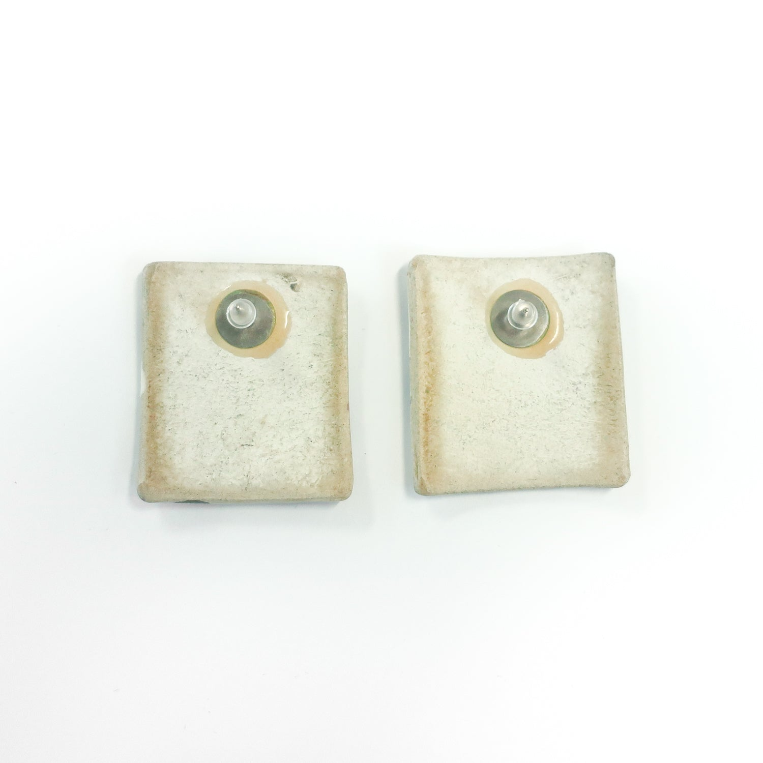Second Room Vintage Clothing. Vintage rectangular white ceramic earrings with hand painted watercolor abstract design; 4.2 cm tall and 3.9 cm wide. As these are hand painted, each one is slightly different. Please note that these are ceramic, and therefore fragile. Original earring backs have been replaced with new, clear silicone backings. Free North American shipping on all orders.