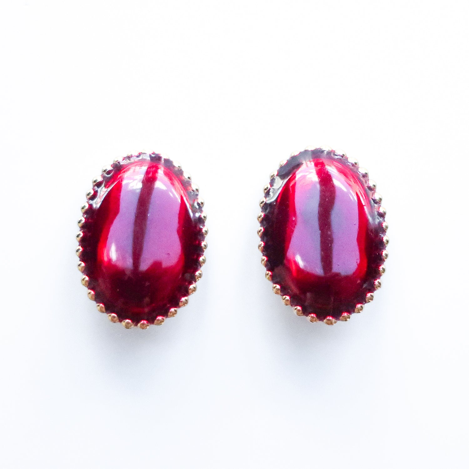 "Second Room Vintage Clothing. Vintage dark red oval earrings, with gold tone dotted trim. Earrings are 7/8"" wide and 1-1/4"" tall. Original earring backs have been replaced with new, clear silicone backings. Free North American shipping on all orders."