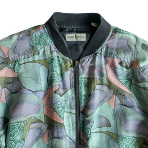 Second Room Shop Vintage. Shop vintage, shop sustainable. Vintage silk bomber jacket with green, pink, and purple pastel abstract pattern. Zipper closure with 2 front pockets, 1 inside pocket, and black ribbing details. This is a men's medium, but would fit a woman as well, sizes Small to Large, depending on how oversize you would like the fit.