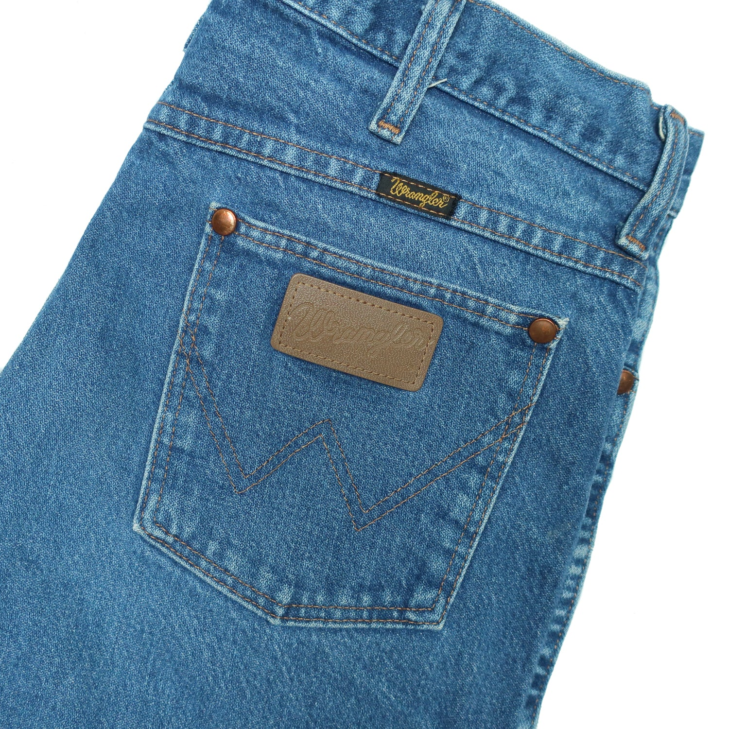 "Second Room Vintage Clothing. Beautifully worn in medium blue wash, straight leg Wrangler jeans. Five pocket style with copper/brass hardware, zipper fly and button, 12"" rise and Wrangler patch on back pocket. Free North American shipping on all orders."