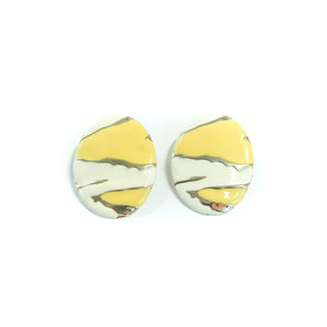 "Second Room Vintage Clothing. Vintage oval, white and yellow enamel painted earrings with abstract design and gold tone details. Earrings are 1.5"" wide and 1.75"" tall. Original earring backs have been replaced with new, clear silicone backings. Free North American shipping on all orders."