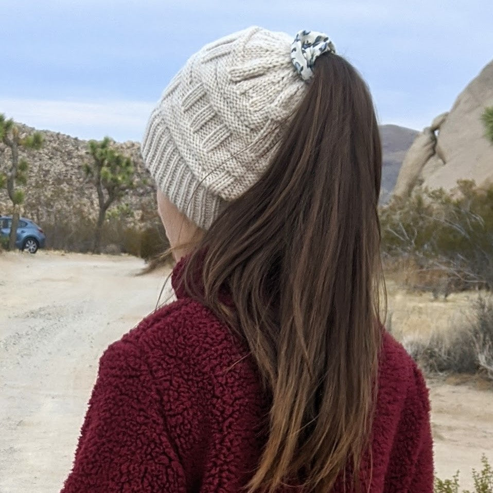 girl showing back of beanie