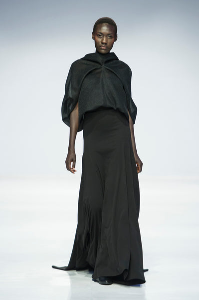 Black sculptural draped mesh top over full length skirt