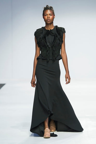 Black sleeveless jacket with fringe detail over full length skirt