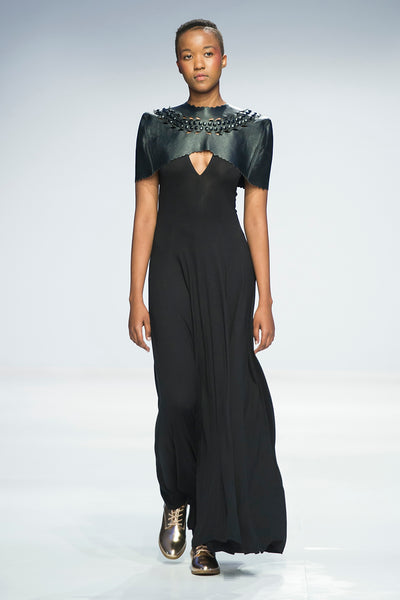 Black leather caplet with laser cut and button detail over v-neck full length dress