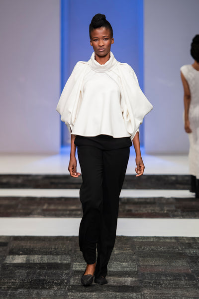 White flared jacket with drapped statement sleeves ove black trousers