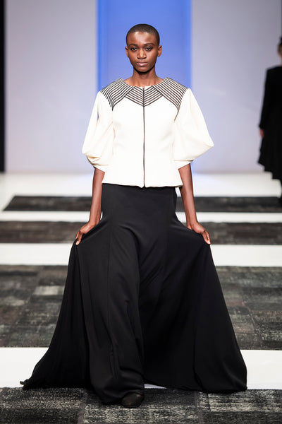 White wool jacket with statement sleeves and ribbon detailing over floor length black skirt