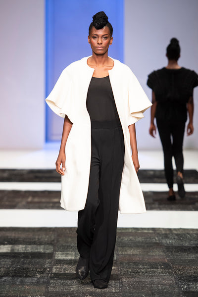 White wool cape sleeve coat over black trousers and top