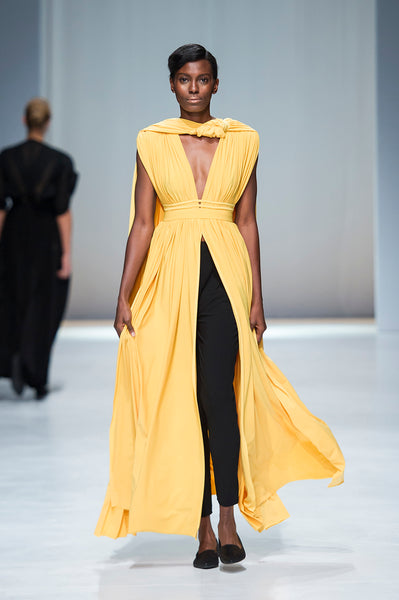 Yellow full length dress with soft draping over black leggings