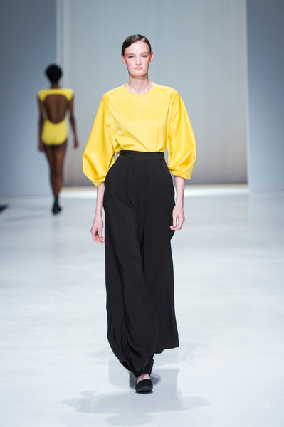 Yellow statement sleeve blouse with black wide legged trousers