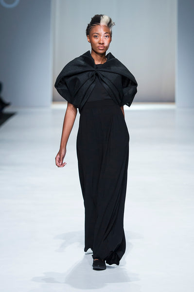 Black top with draped detail over black trousers