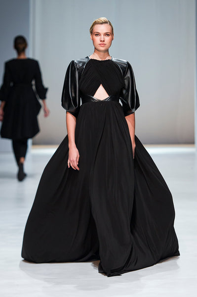 Black full length dress with leather shoulders and sleeves and keyhole and draped detail
