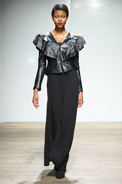 Black leather jacket with layered ruffle detail over shoulders with wide leg pants