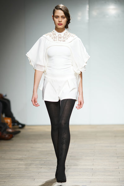 White top with layered chiffon sleeves and beaded bib over shorts