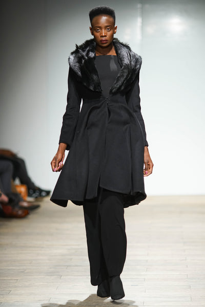 Black wool hour glass coat with springbok fur collar over trousers