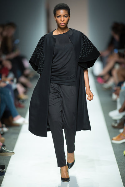Black cape sleeve jacket with laser cut details worn over top and skinny cut trousers