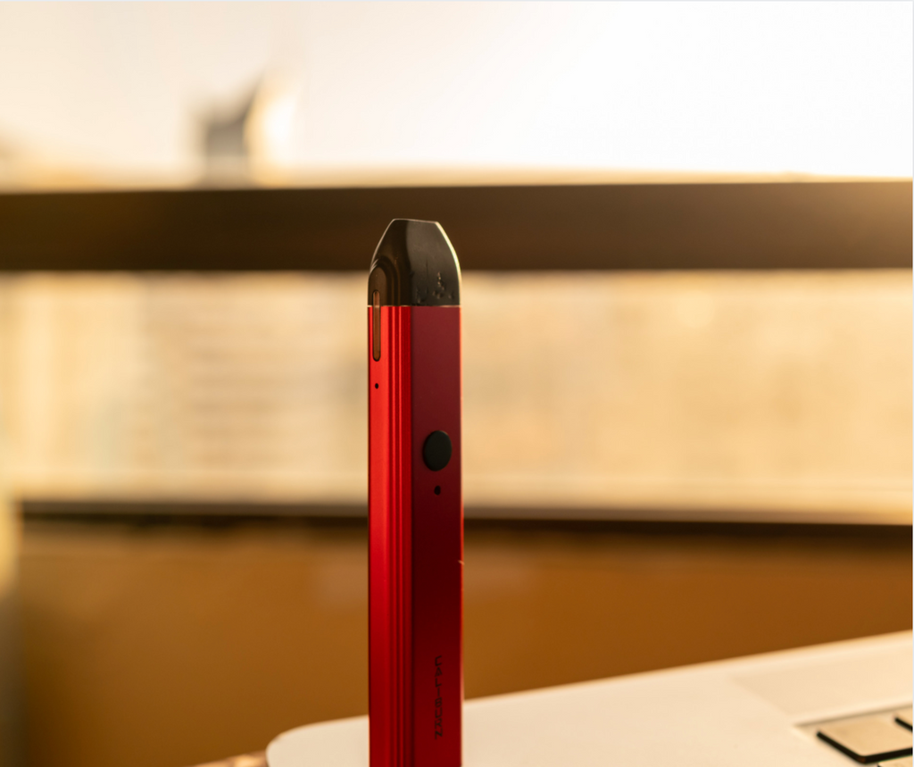 A red vape device on a table