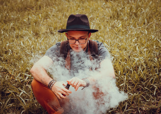 A man sat in a field exhaling vapour