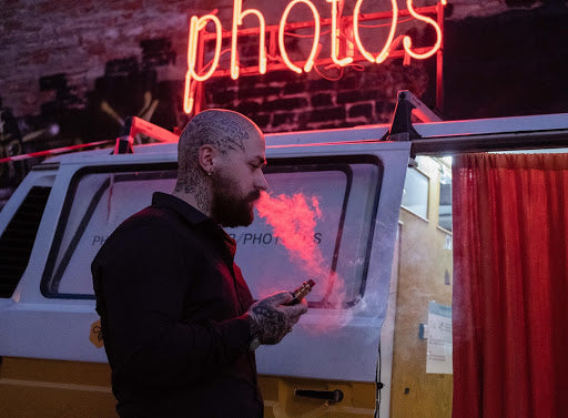 A tattooed man with a shaved head vaping