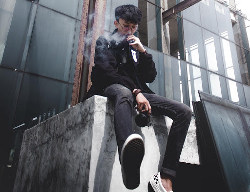 A guy sat in the city vaping