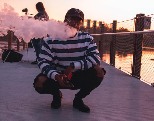 A man crouched down by water vaping