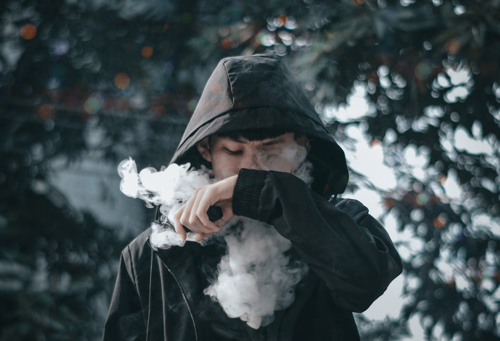 a man vaping with a large cloud