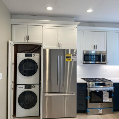 Walk through pantry used for stackable washer and dryer in the kitchen