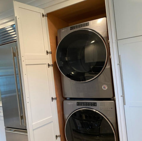Stackable washer and dryer hidden within the kitchen