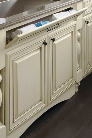 Tilt out tray for a kitchen sink base cabinet