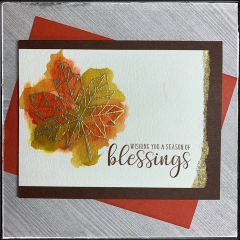 "the handmade card from 1cre8ivemess has a watercolor base and gold heat embossing. a blend of colors representing the changing colors on the leaves in autumn is delicately placed near a stamped sentiment which reads ""wishing you a season of blessings""."