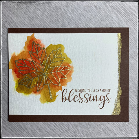 a flatlay view of card 13/100-2 of #the100dayproject. a watercolored leaf in shades of reds, oranges and greens under a layer of gold embossing. a torn edge and stamped sentiment complete the card front.