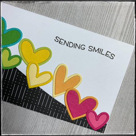 """close up detail of the right side of the card, including the rainbow die-cuts that are green, yellow, orange and pink. in the right corner is the stamped sentiment """"sending smiles."""""""