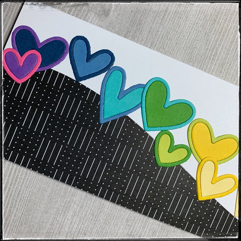 up close detail of the left side of the card base. the dots and lines are evident on the patterned paper background and the various sizes of hearts can be seen from left to right in shades of purple, dark and light blue, aqua, and two shades of green.