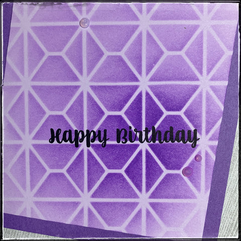 detailed photo of the bottom right corner of this handmade purple stenciled birthday card. the stencil features a square pattern with horizontal lines that almost resemble the outline of an envelope from the back. crisp black letters spell out happy birthday.