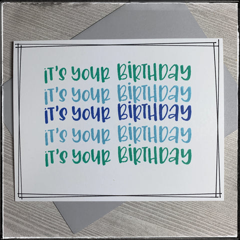 """""""it's your birthday"""" is stamped five times in a row horizontally in shades of aqua and blue. thin black lines surround the perimeter of the white card front. a light grey envelope is included with this card and creates a nice background."""