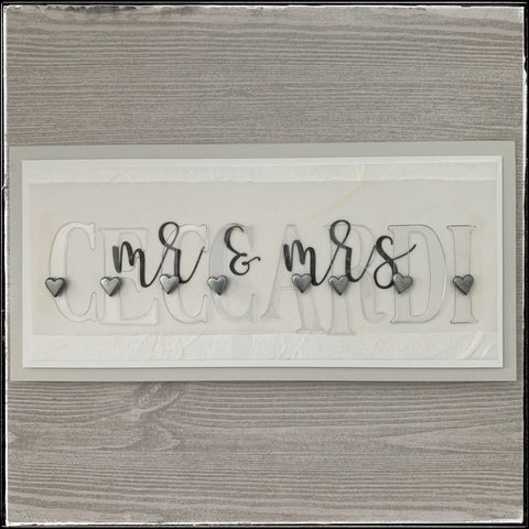 the flat-lay photo of the mr & mrs card for a wedding this past weekend. layers of specialty white paper create a gorgeous background under clear acetate letters spelling the newlywed's last name, with one tiny silver heart on each letter.