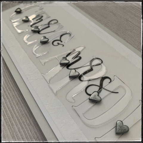 an angled view of this handmade wedding card. the clear letters have a beautiful shine to them that's visible in the right lighting.