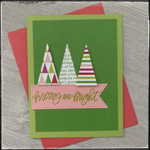 """a pink envelope lays under a green card base that's layered with three small triangles in a variety of patterns. the sentiment """"merry and bright"""" is accompanied on a pale pink banner which matches the patterned paper."""