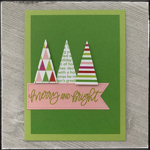 """flat lay of the card front with three triangle trees and a banner with the sentiment """"merry and bright""""."""