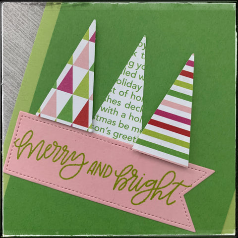 detailed photo of the three small triangle trees, along with the sentiment. patterns on the trees include smaller triangles, christmas text and multi-colored stripes.