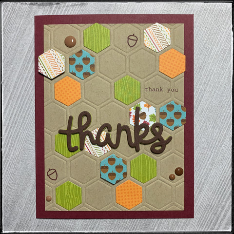 "a flat-lay photo of the handmade thanks card featuring a variety of doodlebug design products including patterned papers and enamel dots. a large die-cut word ""thanks"" has been double-stacked with cardstock and fun foam for a wonderful autumn seasonal card."